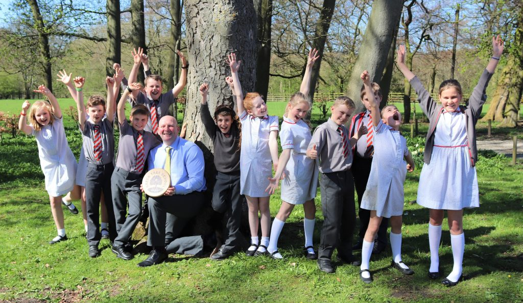 Excited pupils celebrating their Gold Award with Headteacher Mr Martin