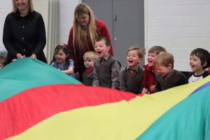 Children smiling as they pull the parachute up and down