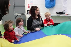 Children and teacher enjoying using the big parachute