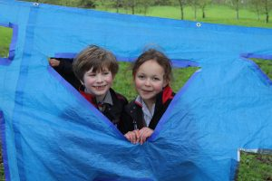 Two schoolchildren smiling during their forest schools lesson