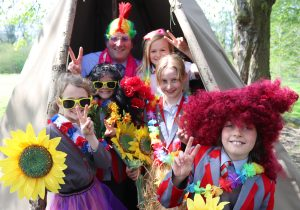 Headteacher and pupils dressed in festival wear promoting school music festival