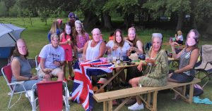 Family in royal family masks celebrating wedding of Prince Harry and Meghan Markle
