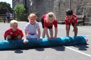 Primary school children rolling out felt on the playground