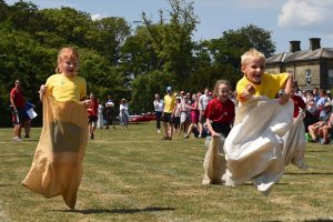 Young children enjoying a sack race on their school's sports day