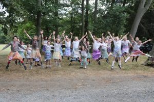 Group shot of all children jumping in the air in their handmade kilts