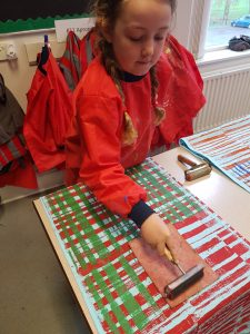 Primary school pupil printing with lino printing block onto fabric