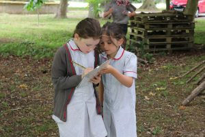 Two girls from Ilkley Primary working with a clipboard in a woodland area