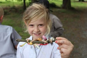 Ilkley Primary Schoolgirl showing camera a stick she has decorated with flowers and feathers