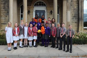 Ghyll Royd pupils with choir members from the Singing Children of Africa on the front steps of Greystone Manor