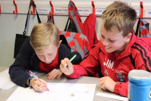 Ghyll Royd School boys look closely at a fossil and write down what animal they think it is