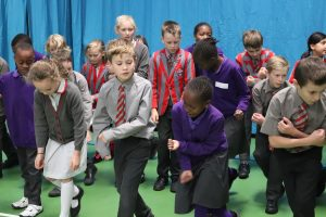 Choir members teaching Ghyll Royd pupils a dance routine to 'This is Me'.