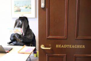 Eeyore visiting Ghyll Royd School sitting behind headteacher Mr Martin's desk