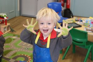 Ilkley Nursery boy smiling holding up his hands covered in green paint.