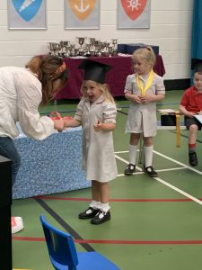Ilkley Nursery child smiling as she is presented with a leaving gift at her nursery graduation