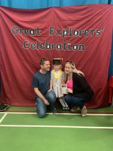 Ilkley Nursery child posing with parents at her nursery graduation