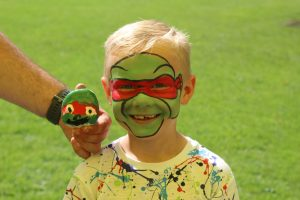 Ilkley Primary school child with face paint and matching painted pebble