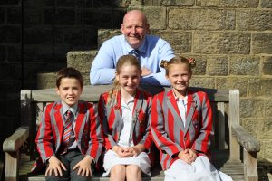 Headteacher David Martin sat on bench with Head pupils