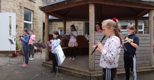 Year 5 children playing the recorder in the school courtyard for our Palm Court concert