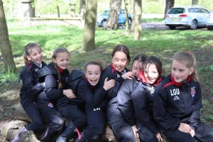 A group of smiling girls enjoying outdoor learning