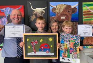 Ilkley Primary - William T holding up his National Art Award piece 'Caravanning on the Moon' next to Headteacher David Martin and Art teacher Keeley Smith